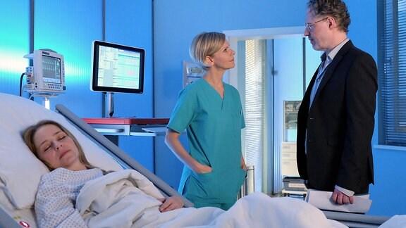 Kathrin Globisch spricht im Patientenzimmer mit einem Mann.