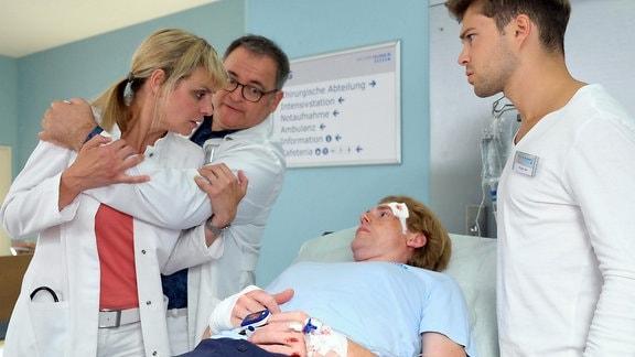 Kris Haas (Jascha Rust, re.) und Hans-Peter Brenner (Michael Trischan, 2.v.li.) bringen den an Jennes Unfall beteiligten Julian Kessler (Johannes Heinrichs, 2.v.re.) in die Chirurgie, als Dr. Lea Peters plötzlich auf sie zustürmt.