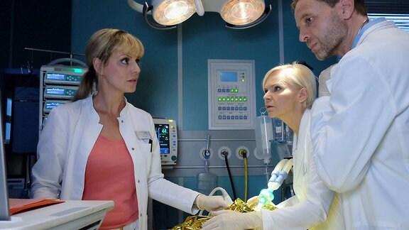 Dr. Lea Peters (Anja Nejarri, li.), Dr. Kathrin Globisch (Andrea Kathrin Loewig, 2.v.re.) und Dr. Kai Hoffmann (Julian Weigend, re.) kämpfen um das Leben eines schwerverletzten Patienten.