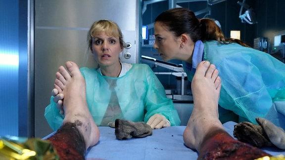 Dr. Lea Peters (Anja Nejarri, li.) entdeckt bei der Untersuchung eine Narbe, die von einem Blitzschlag stammt. Lea wird bewusst, dass es sich bei dem Mann um ihren Freund Jenne handelt.