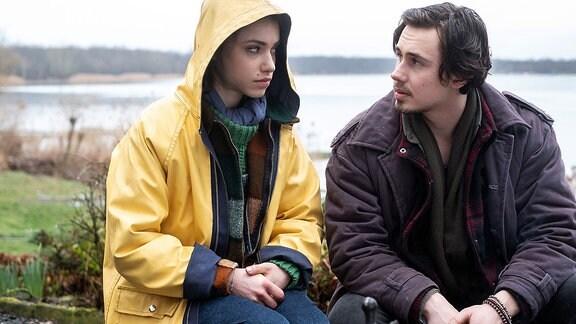 Emma Brückner (Vivien Sczesny) und Nils Winter (Yannic Eilers) sitzen im Regen am Bootshaus.