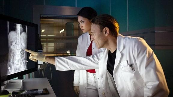 Dr. Martin Stein (Bernhard Bettermann) zeigt Dr. Lilly Phan (Mai Duong Kieu) das Röntgenbild.