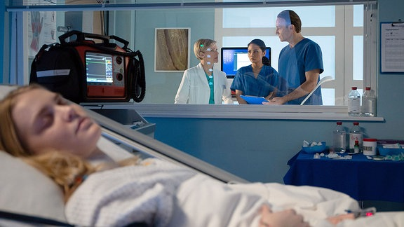 Dr. Kathrin Globisch, (Andrea Kathrin Loewig, li.) und Dr. Martin Stein (Bernhard Bettermann, re.) besprechen Infos über ihre Patientin (Vanessa Kahl, vorn, liegend)