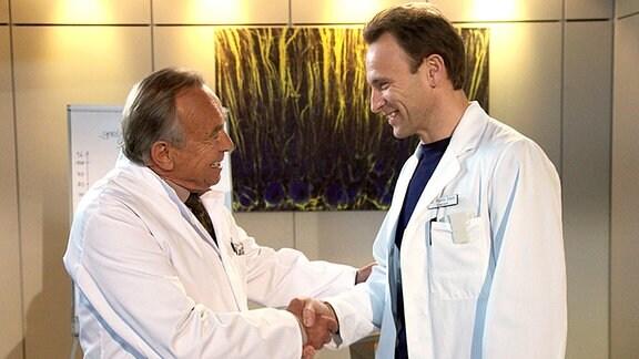 Prof. Simoni (Dieter Bellmann, li.) gratuliert Dr. Martin Stein (Bernhard Bettermann, re.). Er übernimmt interimsweise den Chefarztposten von Dr. Roland Heilmann, der sich mehr um seine an Brustkrebs erkrankte Frau kümmern möchte.