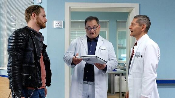 Oliver Paul (Marc Ben Puch, li.) hat ein urologisches Problem. Dr. Kaminski (Udo Schenk, re.) überlässt Hans-Peter Brenner (Michael Trischan, mi.) zum ersten Mal die Alleinbetreuung eines Patienten. Hans-Peter fühlt sich geschmeichelt und stürzt sich voller Elan in seine Aufgabe.