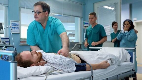 Hans-Peter Brenner (Michael Trischan, li.) und Dr. Kaminski (Udo Schenk, 3.v.re.) haben bei Oliver Paul (Marc Ben Puch, liegend) eine urologische Routine-OP durchgeführt. Doch während des Eingriffs gab es Komplikationen und nun hat er sogar einen Herzstillstand. Olivers Frau Katharina (Nora Jokhosha, re.) ist in Sorge: Wie kann das bei einem Routine-Eingriff passieren? Kaminski bitte die Schwester (Komparsin, 2.v.re.) Katharina raus zu bringen.
