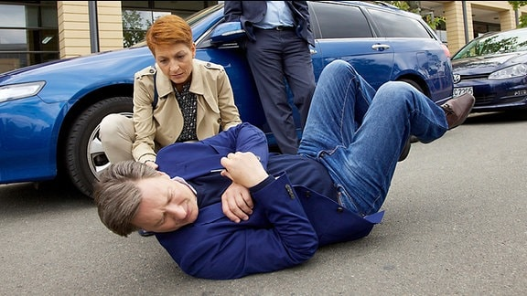 Täter und Opfer: Als Roland Heilmann (Thomas Rühmann, hinten) den Stalker Wolfgang Gebert (Martin Armknecht, vorn) erneut vor der Klinik herrumlungern sieht, platzt ihm endgültig der Kragen. Er zerrt ihn aus seinem Auto und nach einer kurzen Rangelei liegt Gebert verletzt am Boden. Pia Heilmann (Hendrikje Fitz, li.) ist schockiert über das Verhalten ihres Mannes und eilt ihrem Stalker zu Hilfe
