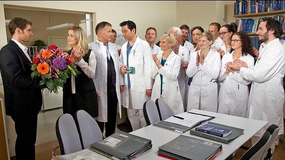 Dr. Niklas Ahrend (Roy Peter Link) wird von Sarah Marquardt (Alexa Maria Surholt) und der gesamten Ärzteschaft verabschiedet
