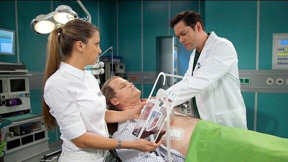 Paul Greiner (Mirco Reseg, liegend), Oberschwester Arzu (Arzu Bazman) und Dr. Philipp Brentano (Thomas Koch)