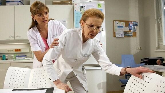 Oberschwester Ingrid (Jutta Kammann, re.) hat seit einiger Zeit Rückenschmerzen. Da sie insgeheim befürchtet, etwas mit den Bandscheiben zu haben, was ihre Arbeit in der Sachsenklinik unmöglich machen würde, verdrängt sie die Schmerzen. Erst als ihr in immer kürzeren Abständen das linke Bein wegknickt, beschließt sie, sich untersuchen zu lassen. Schwester Yvonne (Maren Gilzer, li.) ist besorgt um Ingrid.
