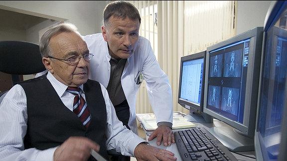 Professor Simoni (Dieter Bellmann, li.) und Dr. Roland Heilmann (Thomas Rühmann, re.) haben die Untersuchungsergebnisse der Oberschwester bekommen. Simonis schlimmste Befürchtungen sind wahr geworden. Roland hat Ingrid schon einmal operiert. Nun ist die Verengung ihres Wirbelkanals zurückgekehrt. Für Simoni kommt eine erneute Operation nicht in Frage, das Risiko einer Lähmung ist zu groß. Roland hingegen, will die Möglichkeit einer OP nicht ausschließen.
