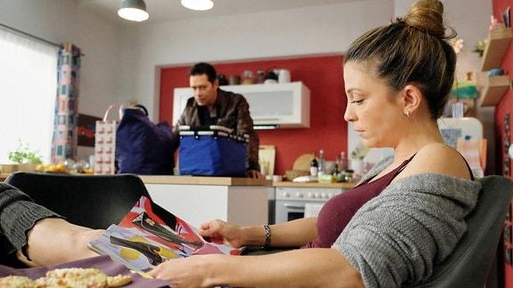 Eine Frau liest mit hochgelegten Beinen eine Zeitung. Im Hintergrund steht ein Mann mit vollen Einkaufstüten und guckt geschafft.