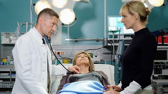 Eine Frau liegt im Krankenbett, Ein Arzt kümmert sich um sie. Eine weitere Frau steht auf der anderen Seite des Bettes.