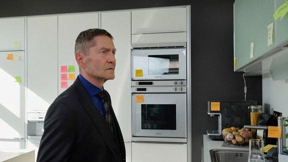 Dr. Kaminski schaut irritiert auf die Küchenzeile.