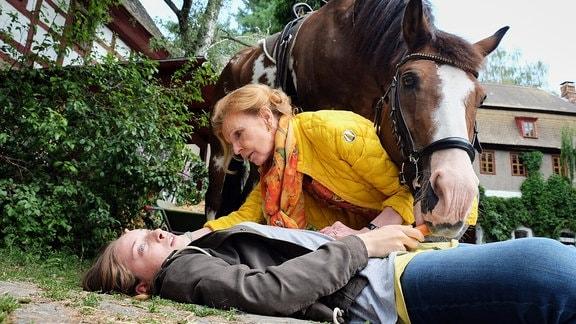 Ingrid Rischke hilft Luna, die vom Pferd gefallen ist.