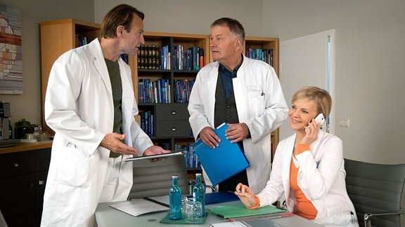 Kathrin telefoniert im Ärztezimmer, Roland und Martin stehen im Hintergrund.
