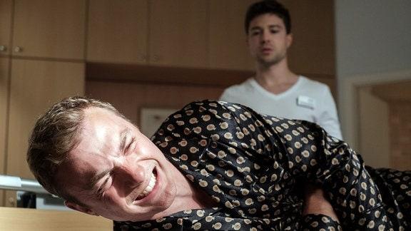 Als Pfleger Kris Haas (Jascha Rust, hinten) Dr. Clemens Seidel (Moritz von Zeddelmann, vorn) das Abendessen bringt, liegt der Gesundheitsdezernent auf seinem Bett und krümmt sich vor Schmerzen.