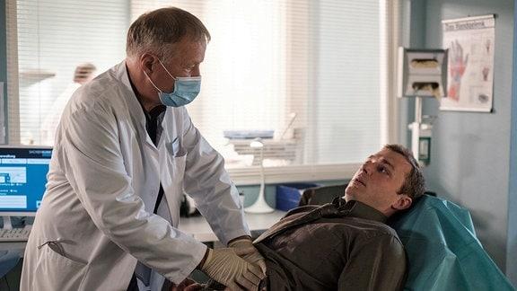 Dr. Clemens Seidel (Moritz von Zeddelmann, re.), Gesundheitsdezernent und selbst Internist, hat seit geraumer Zeit Schmerzen im Bauch und kommt mit seinen Selbstdiagnosen nicht weiter. Da die Schmerzen immer stärker werden, begibt er sich in die Hände von Dr. Roland Heilmann (Thomas Rühmann, li.).