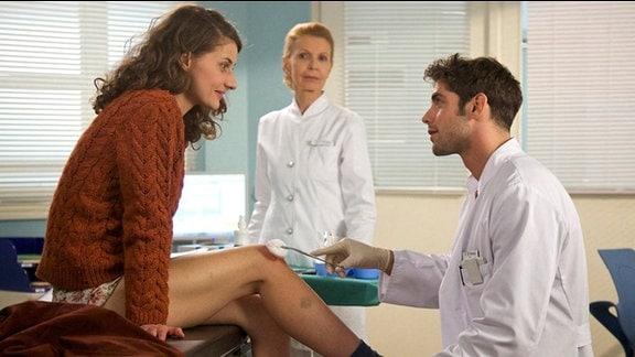 Die Kindergärtnerin Britta Leitner wird von Dr. Niklas Ahrend und Oberschwester Ingrid am Knie untersucht.