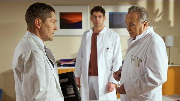 Dr. Niklas Ahrend mischt sich in ein Patientengespräch zwischen Professor Gernot Simoni  und Dr. Rolf Kaminski ein.