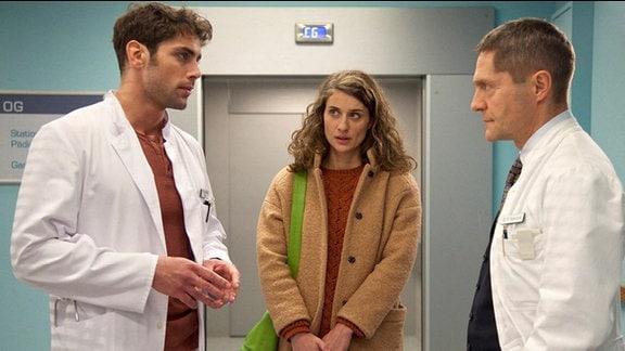 Dr. Niklas Ahrend spricht mit Dr. Rolf Kaminski. Patientin Britta Leitner hört zu.