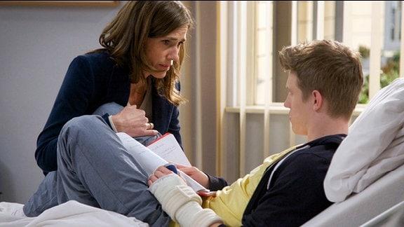 Eine besorgte Mutter sitzt am Krankenbett ihres Sohnes.