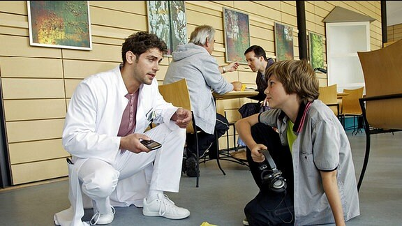 Dr. Niklas Ahrend (Roy Peter Link, li.) nutzt einen Zusammenstoß mit dem Sohn seiner Geliebten Bastian Marquardt (Johann Lukas Sickert, re.), um ihm auf den Zahn zu fühlen. Niklas gibt sich betont lässig und Bastian ist ziemlich begeistert von dem neuen Arzt.