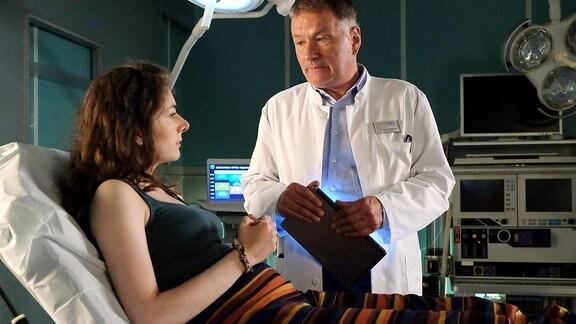 Dr. Roland Heilmann untersucht eine Patientin (Szene aus In aller Freundschaft)