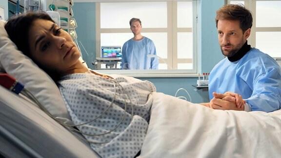 Paul Rabe (Dominik Maringer, re.) ist wütend und verletzt. Er sitzt dennoch am Bett seiner Frau Katja (Pegah Ferydoni, li.).