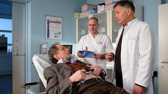 Thomas Bruhnke (Oliver Törner, li.) wird mit Schmerzen in die Sachsenklinik eingeliefert.