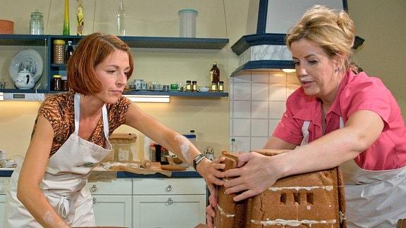 Pia Heilmann (Hendrikje Fitz, li.) und Sarah Marquardt (Alexa Maria Surholt, re.) versuchen sich in der Küche mit Lebkuchenplatten am Bau des Völkerschlachtdenkmals für das Schulfest von Jonas und Bastian.