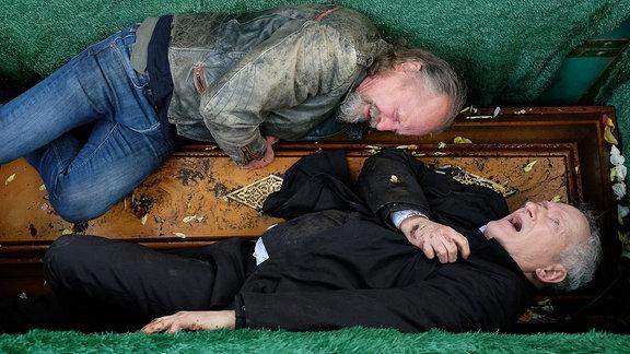 Nachdem die beiden Brüder Thomas (Falk Rockstroh (unten) und Wolfgang Brünn (Paul Faߟnacht, oben) sich nach Jahrzehnten am Grab ihrer Mutter wiedergetroffen hatten, sind sie sofort aneinandergeraten. Die Handgreiflichkeit führte sogar so weit, dass beide ins offene Grab der Mutter gestürzt sind und sich verletzt haben.