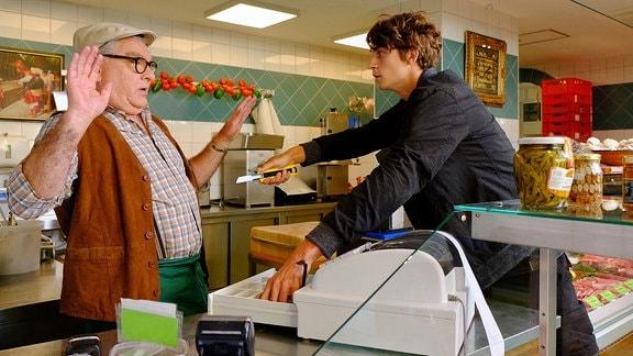 Klaus Scheffler (Klaus Dieter Bange, li.) wird von einem jungen Mann (Tamino Haberland) mit einem Teppichmesser bedroht.