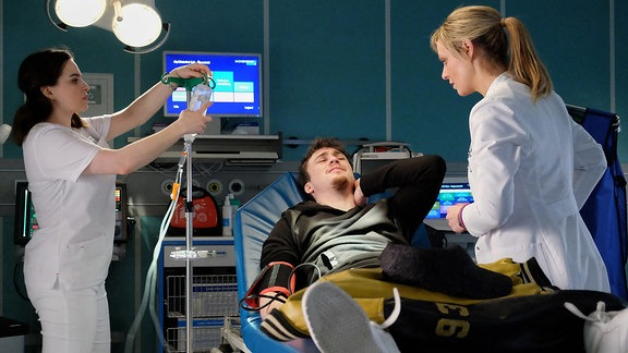 Sebastian Pückler (Justus Johanssen, mi.) wird von Dr. Lea Peters (Anja Nejarri, re.) und Schwester Jasmin (Leslie-Vanessa Lill, li.) versorgt.