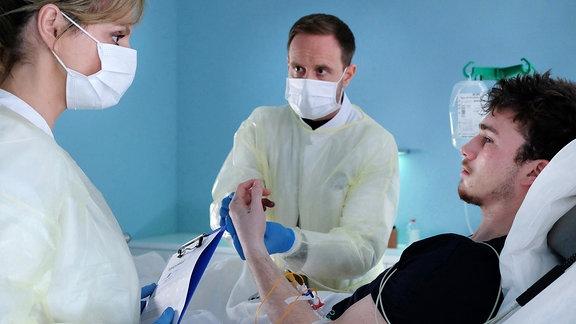 Sebastian Pückler (Justus Johanssen, re.) ist laut Dr. Lea Peters (Anja Nejarri, li.) und Dr. Kai Hoffmann (Julian Weigend, mi.) in einem kritischen Zustand.