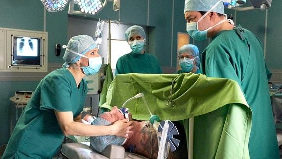 Adrian Walter (Marko Dyrlich, liegend) hat nach seinem Fahrradunfall schwerste Verletzungen. Während der OP kommt es zu Komplikationen. Dr. Kathrin Globisch (Andrea Kathrin Loewig, li.) bittet Dr. Philipp Brentano (Thomas Koch, re.) zu unterbrechen. Als es sogar zum Herzstillstand kommt und Kathrin den Defibrillator ansetzen will, traut sie ihren Augen nicht: Adrian ist wach!