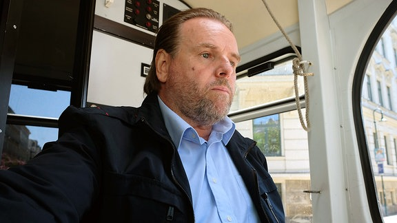 Straßenbahnfahrer Malte Steinhagen (Felix Vörtler) konnte seine Straßenbahn nicht mehr schnell genug bremsen und hat einen Fahrradfahrer umgefahren. Malte sitzt wie versteinert hinter seinem Steuerpult.