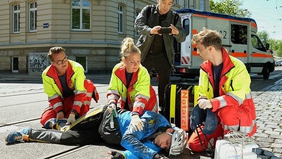Während der Notarzt (Markus Neumann, li.) und seine beiden Kollegen (Jascha Rust (re.) und Sarah Zeising (mi)) den verletzten Fahrradfahrer (Tim Haberland, liegend) versorgen, filmt ein Gaffer (Albrecht Ganskopf) die ganze Zeit mit.