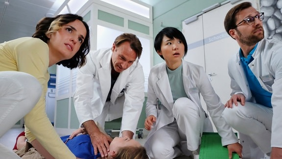 Junge Ärzte beugen sich über eine Pj-lerin, die umgefallen ist.