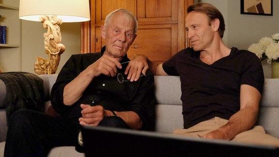 Otto und Martin sitzen gemeinsam auf dem Sofa.