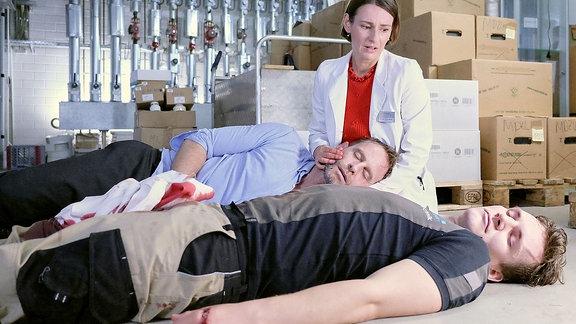 Dr. Maria Weber hält den bewusstlosen Kai Hoffmann fest, daneben der verletzte Hausmeister.