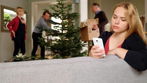 Lisa schaut traurig auf ihr Handy.