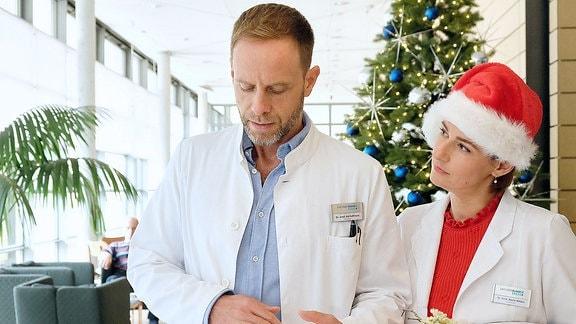 Dr. Maria Weber mit Weihnachtsmann-Mütze und Dr. Kai Hoffmann