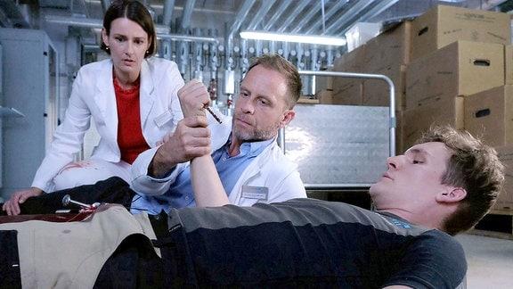 Dr. Maria Weber und Dr. Kai Hoffmann blicken erschrocken als der Verletzte den Bohrer in der Hand hält.