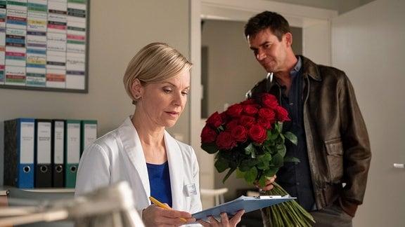 Ein Mann mit einem Rosenstrauß in der Hand für Kathrin Globisch.