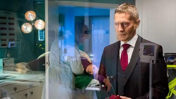 Rolf Kaminski vor einer Glasscheibe.