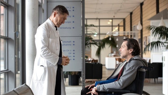 Dr. Kaminski spricht mit Harald Fecht, der im Rollstuhl sitzt.