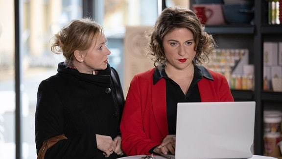 Natalie Döring arbeitet am Computer. Neben ihr steht Marion Fecht.