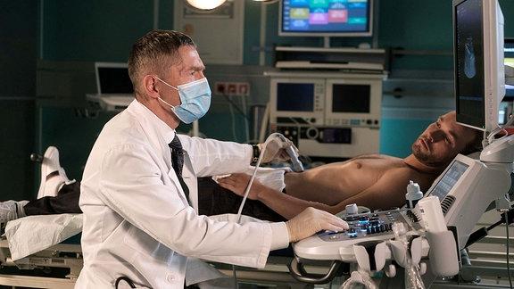 Dr. Kaminski (Udo Schenk, li.) untersucht den Patienten.
