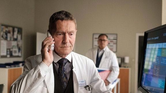 Dr. Kaminski (Udo Schenk, vorn) am Telefon.